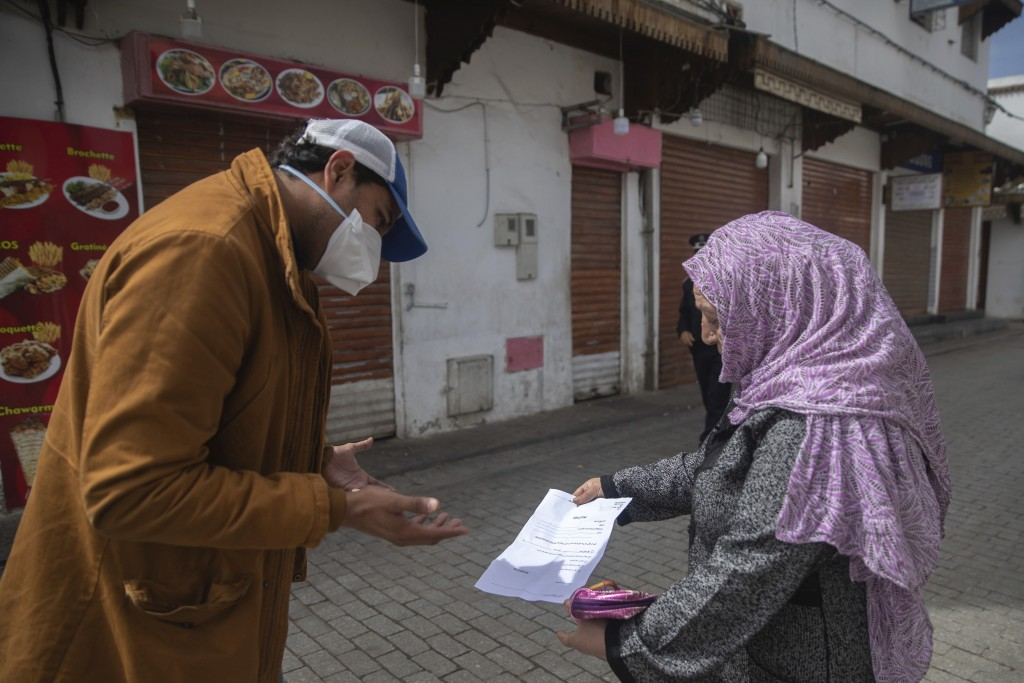 A member of security forces inspects a permit allowing a woman to leave her home, after a health state of emergency was declared and members of the pu...