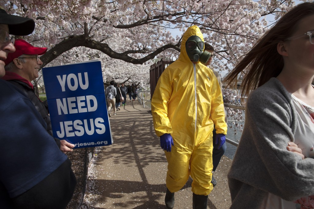 """A 17-year-old who asked not to be named, wears a hazmat suit, gas mask, boots, and gloves as he walks past people holding a sign that says, """"you need ..."""