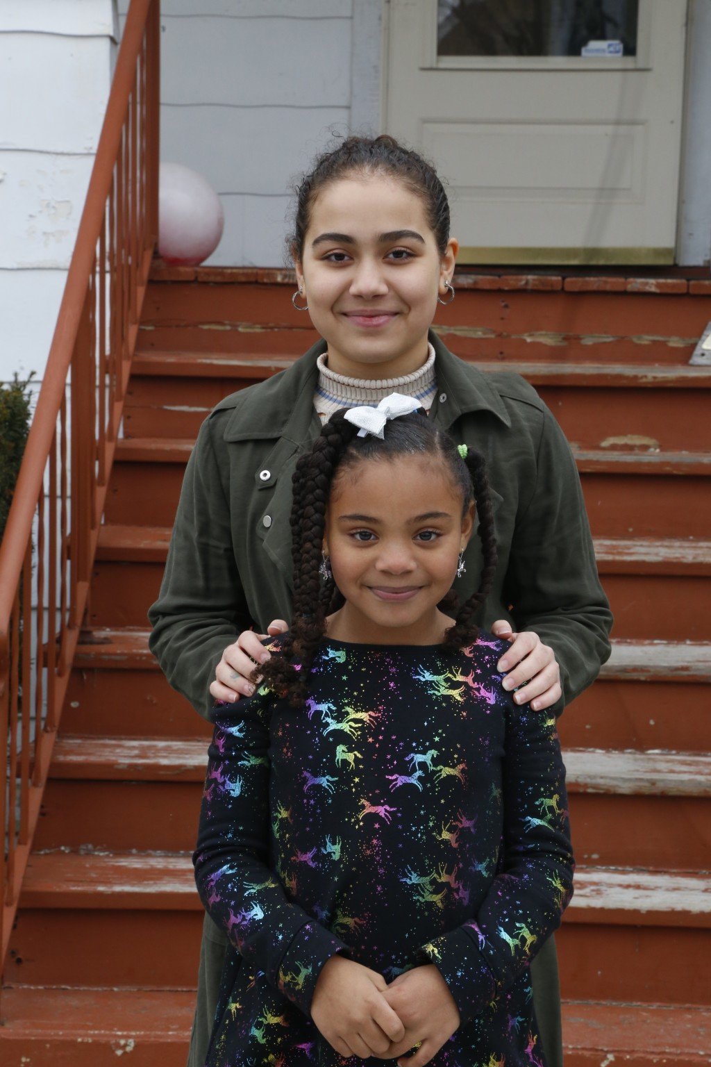 Jalen Grimes, 13, stands behind 7-year-old sister, Sydney, outside their home in Chicago on Sunday, March 22, 2020. Both girls are now doing schoolwor...