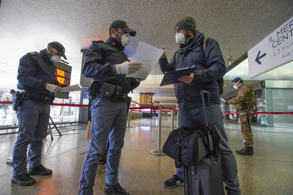 Police officers check passenger's travel documents, at Rome's Termini main train station, Monday, March 23, 2020. For most people, the new coronavirus...