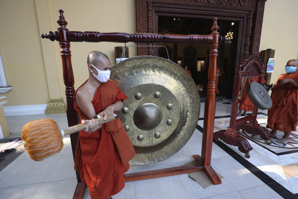 A Buddhist monk strikes a gong at a pagoda in Phnom Penh, Cambodia, Monday, Mar. 23, 2020. Buddhist pagodas in Cambodia on Monday offered prayer, chan...