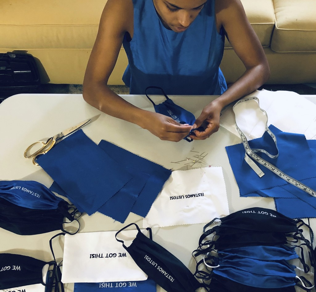 """In this Sunday, March 22, 2020, photo, provided by Christina Hunter, Briana Danyele sews cloth face masks that say """"We Got This!"""" in her mother's livi..."""