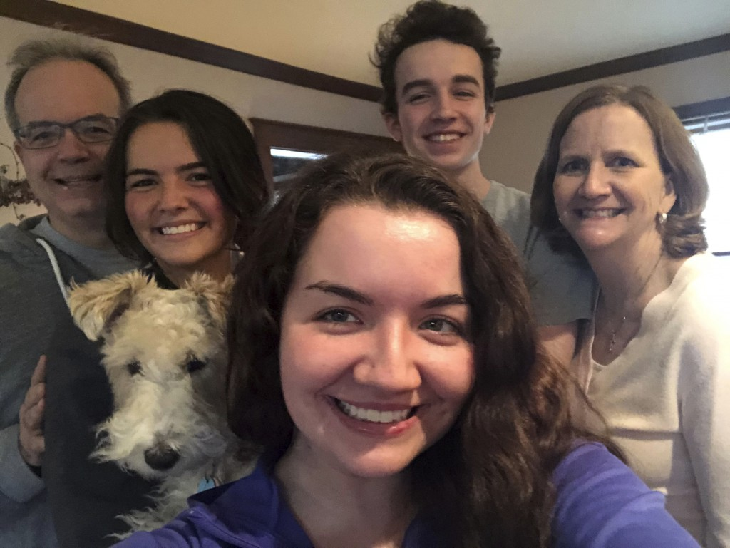In this photo provided by Clare Sulentic, Sulentic, center, takes a family photo on Friday, March 20, 2020, at her parents' home in Dubuque, Iowa. Sul...