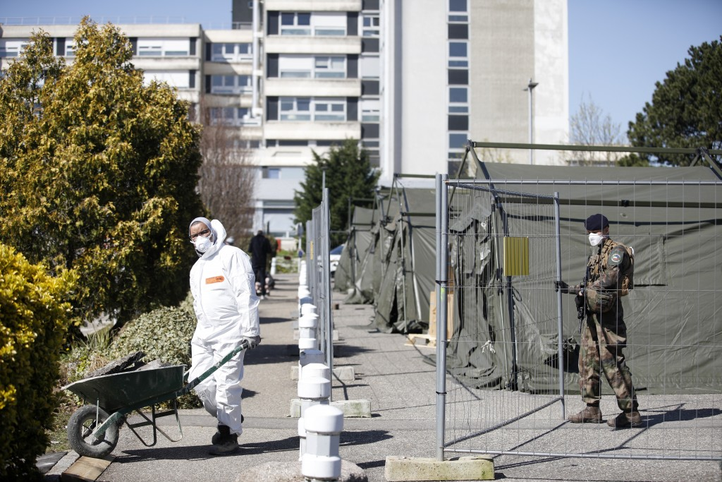 A soldier opens the gate to a worker at the military field hospital built in Mulhouse, eastern France, Monday March 23, 2020. The Grand Est region is ...