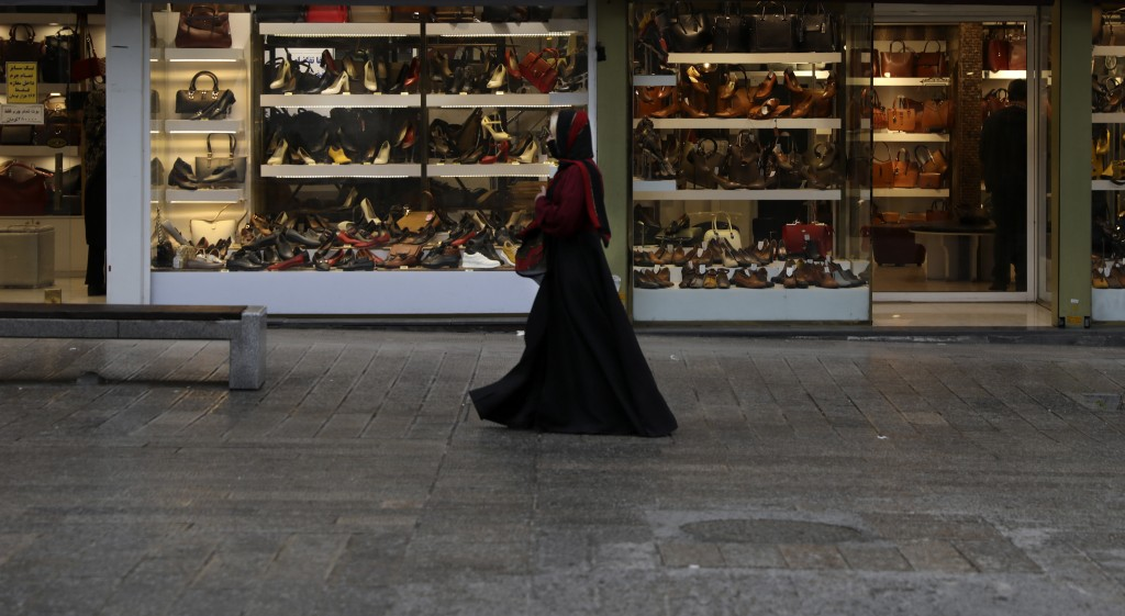 A woman wearing a face mask as a preventive measure against the spread of the new coronavirus walks past shoe shops in a mostly empty street in a comm...