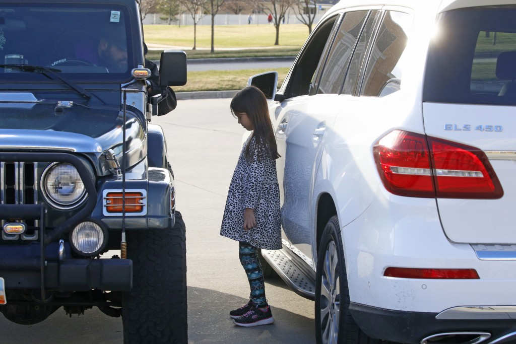 """Father Stephen Tilley, left, sits behind his steering wheel as he listens to the confession of Lily Werner, 8, during """"Meet Me at the Jeep,"""" for a dri..."""