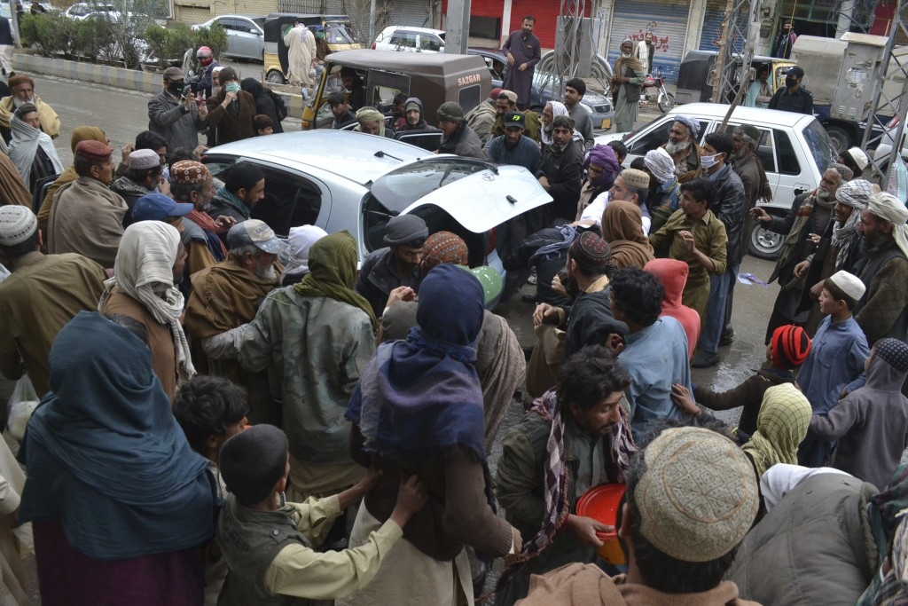 Daily wage workers, jobless due to coronavirus outbreak, rush to a car to receive free food distributed in Quetta, Pakistan, Monday, March 23, 2020. T...
