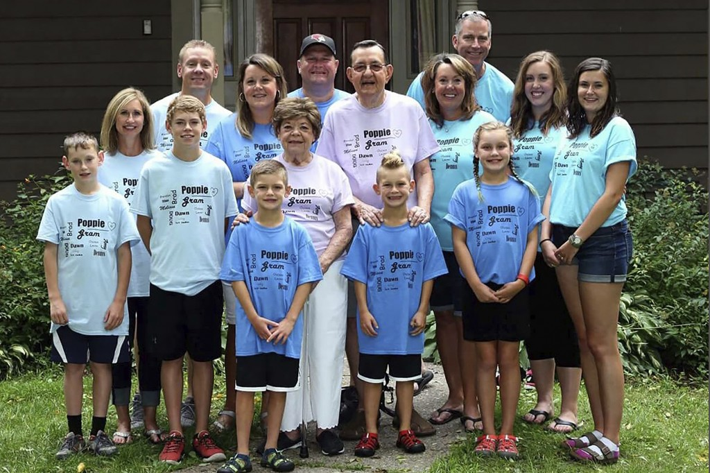 In this August 2016 family photo provided by Dawn Bouska, Charles and his wife, Patricia Recka, purplish shirts, are surrounded by their children and ...