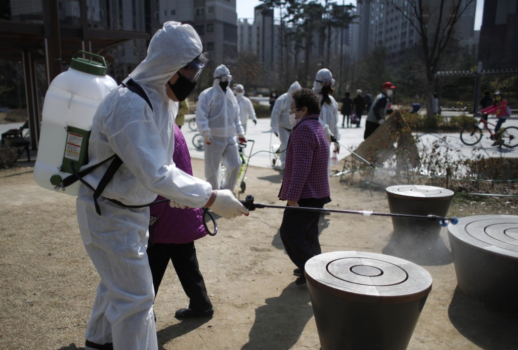 Members of a local residents group wear protective gear as they disinfect a local park as a precaution against the new coronavirus in Seoul, South Kor...