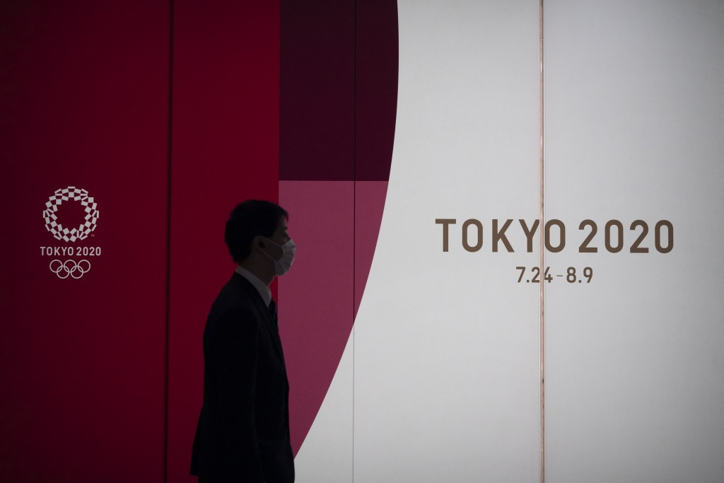 A man walks past a large display promoting the Tokyo 2020 Olympics in Tokyo, Monday, March 23, 2020. The IOC will take up to four weeks to consider po...