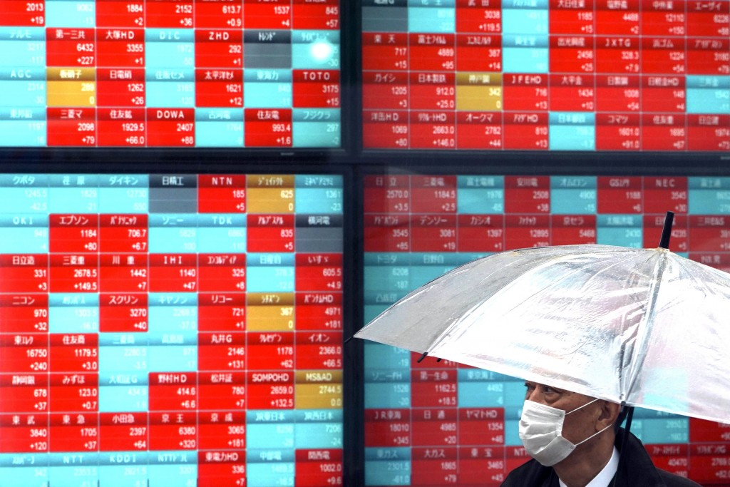 A man with protective mask stands in the rain near an electronic stock board showing Japan's Nikkei 225 index at a securities firm in Tokyo Monday, Ma...