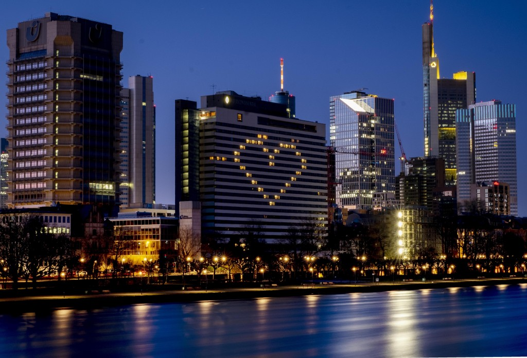 A hotel has switched on the lights in some rooms to form a heart near the buildings of the banking district in Frankfurt, Germany, Sunday, March 22, 2...