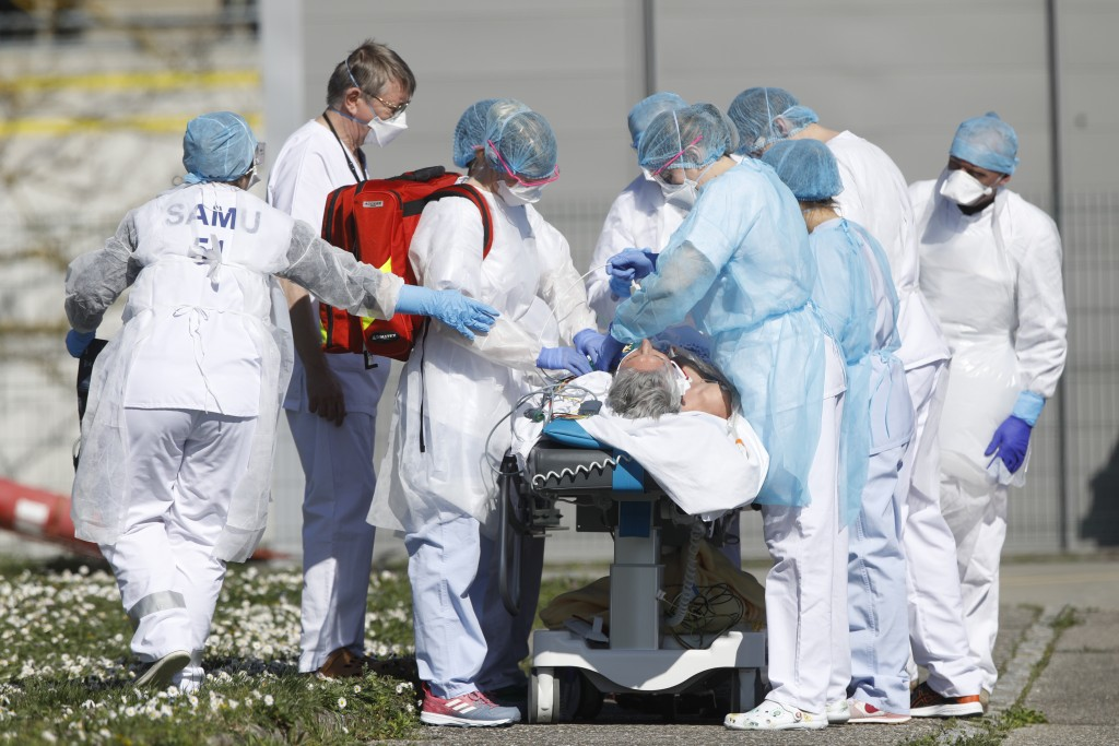 A victim of the Covid-19 virus is evacuated from the Mulhouse civil hospital, eastern France, Monday March 23, 2020. The Grand Est region is now the e...