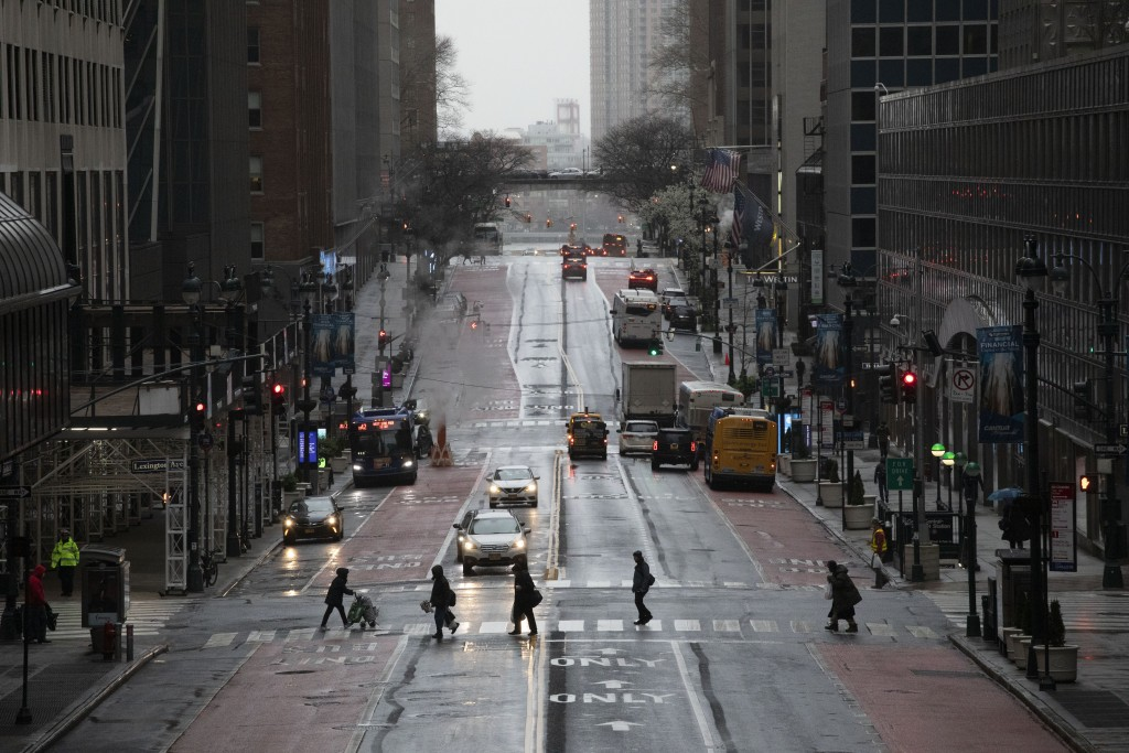 Commuters cross 42nd Street in front of Grand Central Terminal during morning rush hour, Monday, March 23, 2020, in New York. Gov. Andrew Cuomo has or...