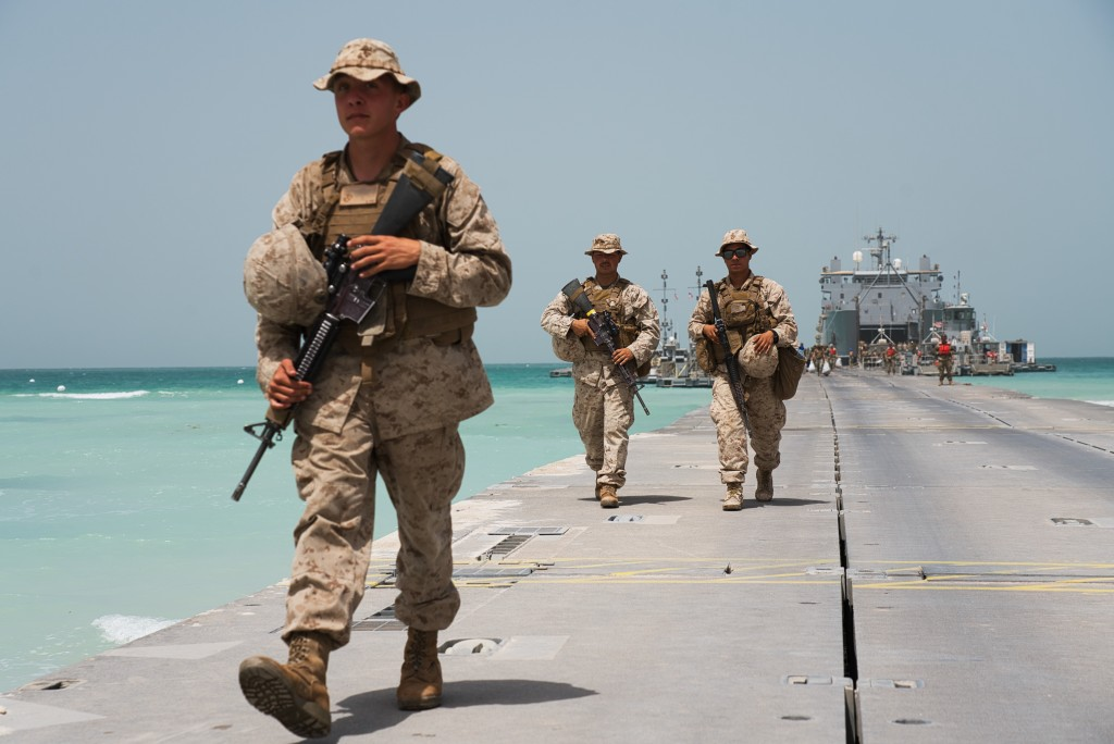 U.S. Marines walk down a removable Trident Pier leading to an American ship docked near an Emirati military base home to a Military Operations and Urb...