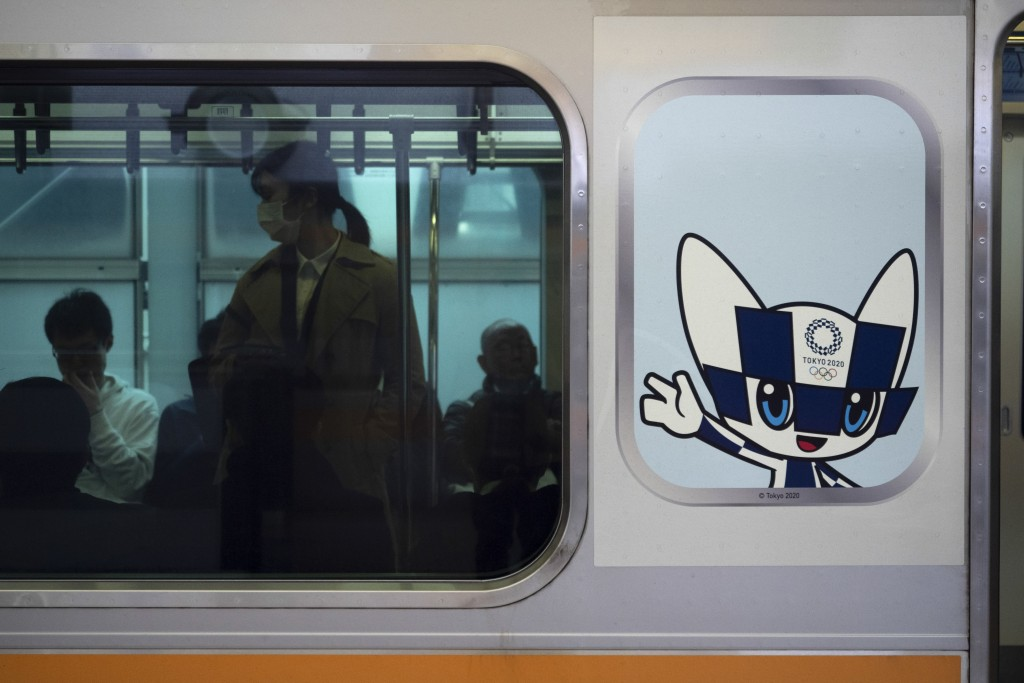 Commuters sit in a train carrying a poster showing the Tokyo 2020 Olympics mascot, Miraitowa, in Tokyo, Monday, March 23, 2020. Japanese Prime Ministe...