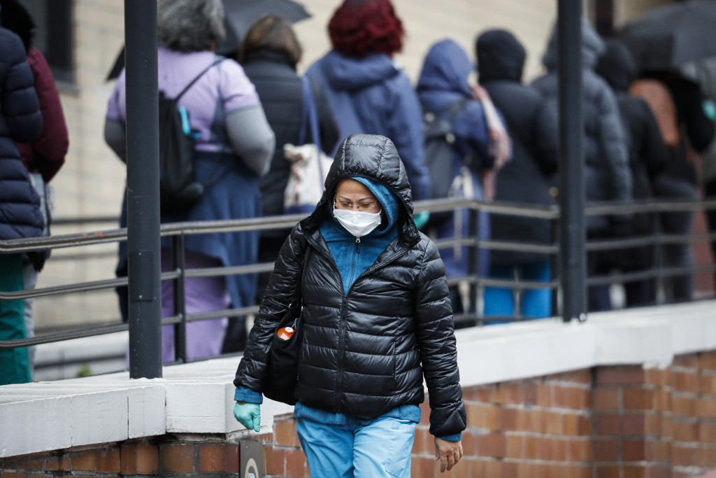 A medical worker wearing a single protective glove and a face mask walks past a line of workers and visitors waiting to be tested for COVID-19, the di...