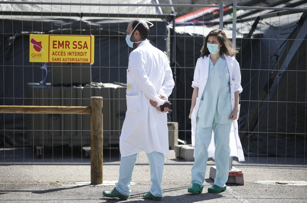 Civil medical staff walk past the military field hospital built in Mulhouse, eastern France, Monday March 23, 2020. The Grand Est region is now the ep...