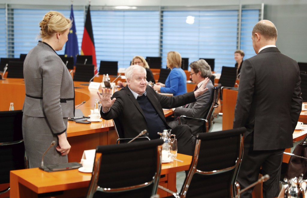 German Interior Minister Horst Seehofer, center, gestures to Finance Minister Olaf Scholz, right, and Minister for Family Affairs, Senior Citizens, Wo...