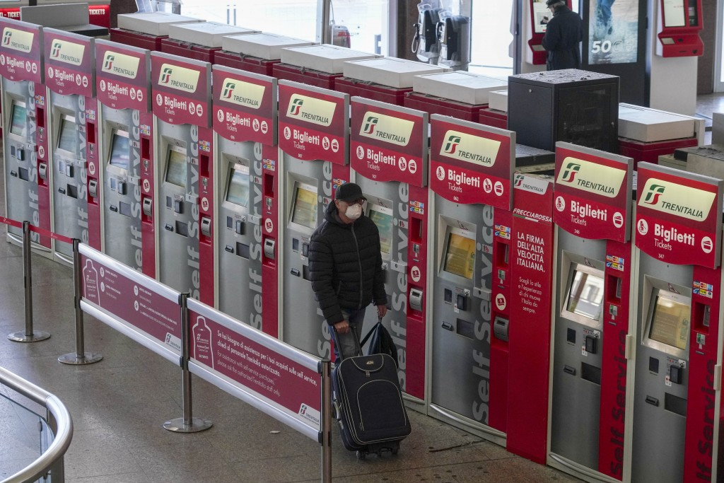 A person walks past ticket machines in an almost empty Termini main train station, in Rome, Monday, March 23, 2020. For most people, the new coronavir...