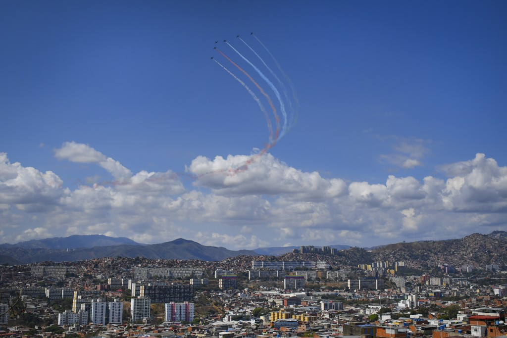 Military planes trail colored smoke as they fly in formation above the city of Caracas, Venezuela, Sunday, March 22, 2020. (AP Photo/Matias Delacroix)