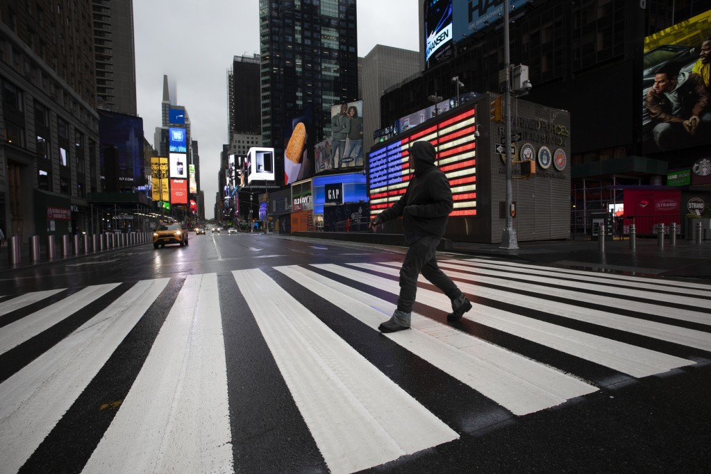 A man crosses the street in a nearly empty Times Square, which is usually very crowded on a weekday morning, Monday, March 23, 2020 in New York. Gov. ...