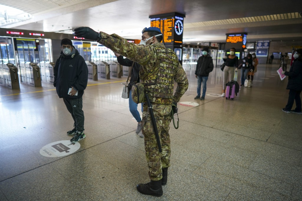 A soldier gives indications to passengers as they line up to have their travel documents checked, in Rome's Termini main train station, Monday, March ...