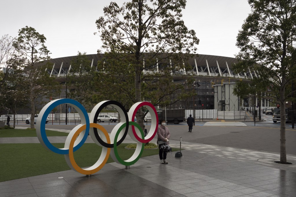 A woman pauses for photos next to the Olympic rings near the New National Stadium in Tokyo, Monday, March 23, 2020. The IOC will take up to four weeks...