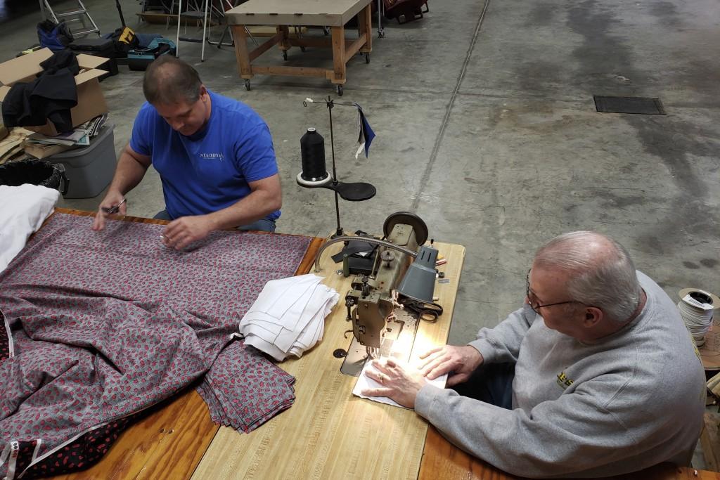 In this Sunday, March 22, 2020 photo, Bill Purdue, left, cuts pieces of fabric while Mike Rice sews them into face masks in Rice's autobody and uphols...