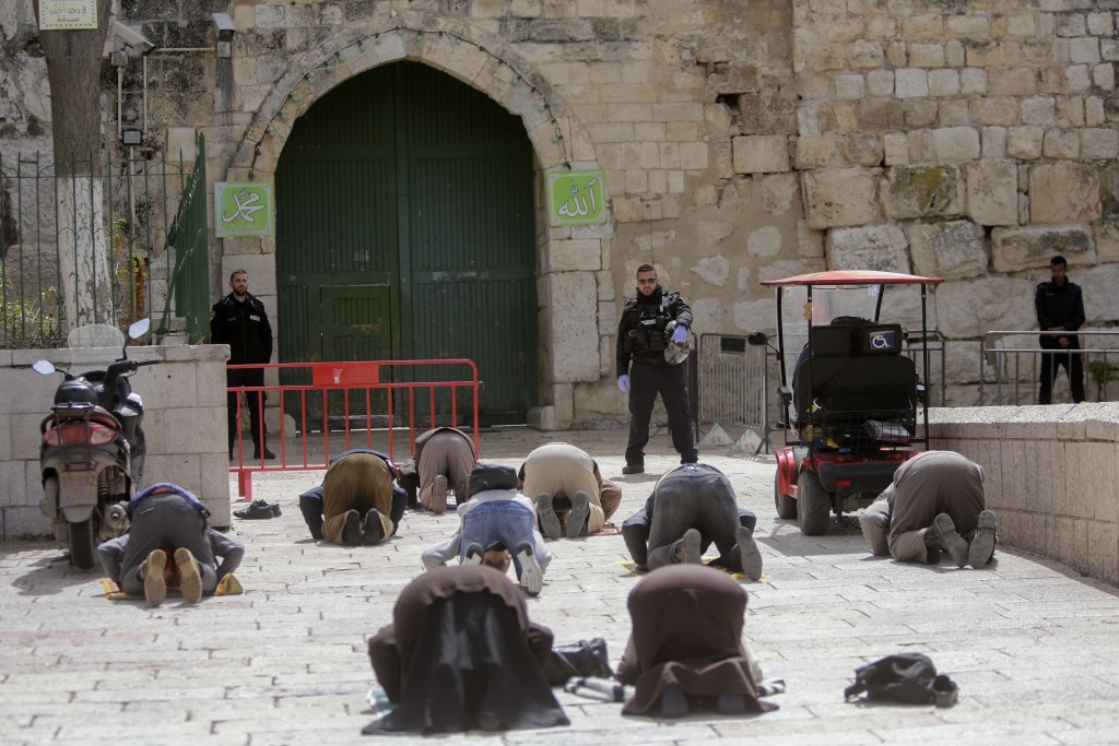 People pray in front of the shuttered gates to al-Aqsa mosque compound as all prayers are suspended to prevent the spread of coronavirus in Jerusalem,...
