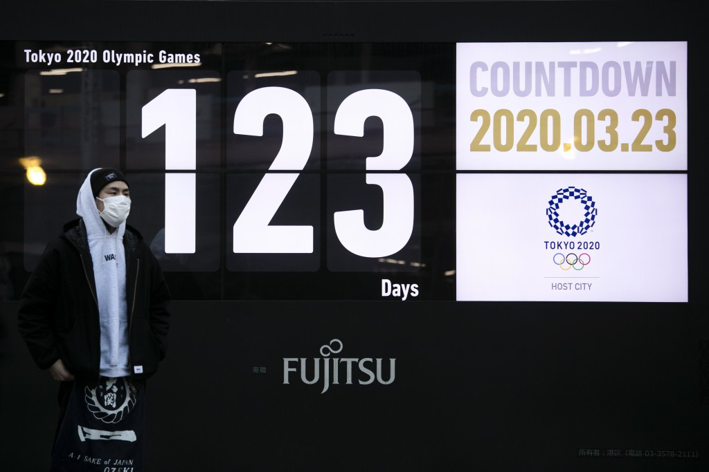 A man stands in front of a countdown display for the Tokyo 2020 Olympics and Paralympics in Tokyo, Monday, March 23, 2020. Japanese Prime Minister Shi...