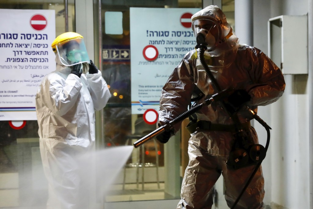 A firefighter sprays disinfectant as a precaution against the coronavirus at the Moshe Dayan Railway Station in Rishon LeTsiyon, Israel, Sunday, Mar...