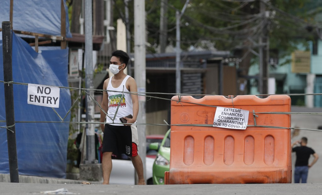 A man wearing a protective mask walks past an area cordoned off for an enhanced community quarantine aimed to prevent the spread of the new coronaviru...