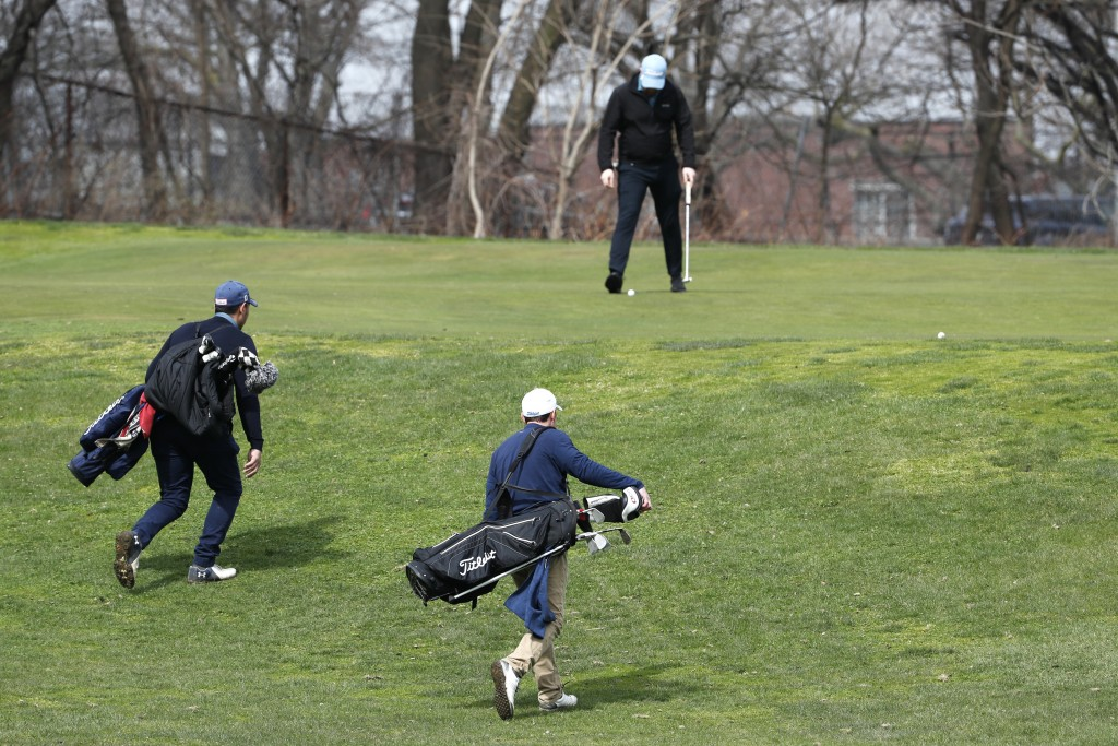 Two golfers approach the green as another golfer finishes his hole at Forest Park Golf Course, Friday, March 20, 2020, in New York. It's not hard for ...