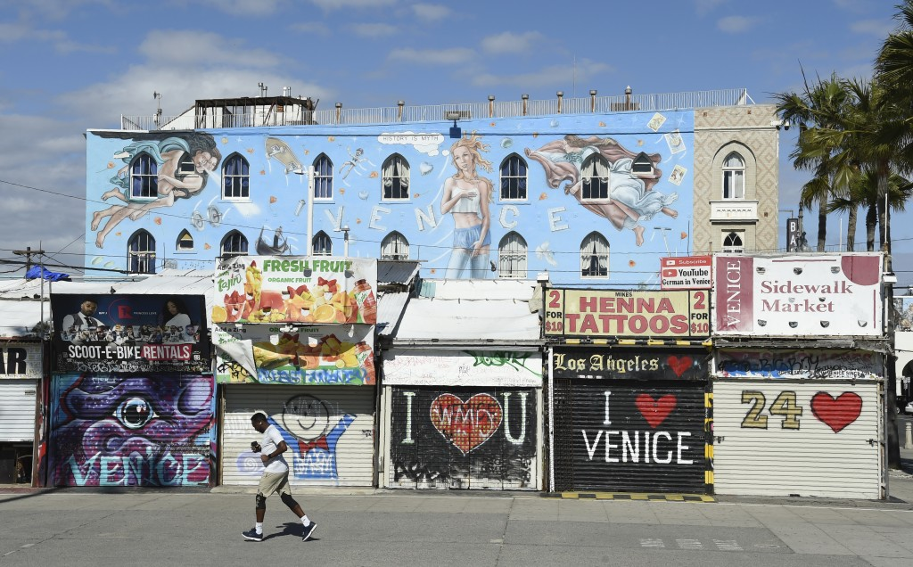 A jogger runs past shuttered shops along Venice Beach Boardwalk, Monday, March 23, 2020, in Los Angeles. Venice Beach Boardwalk was officially closed ...
