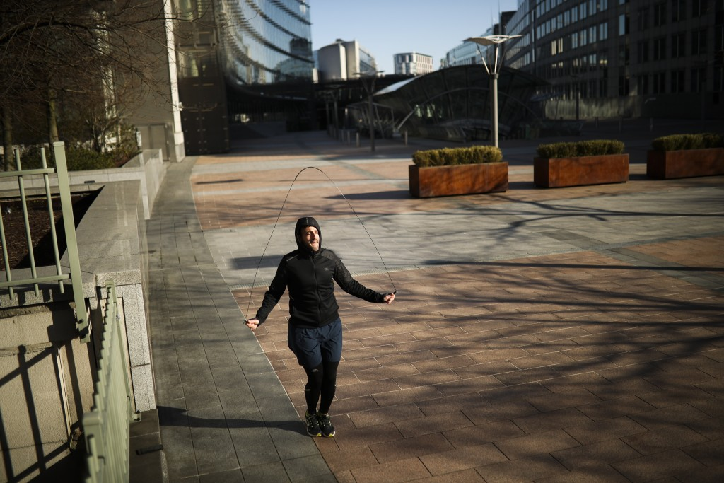 A man jumps rope as he works out in a nearly empty square outside the European Parliament during a partial lockdown ordered by Belgium government in B...