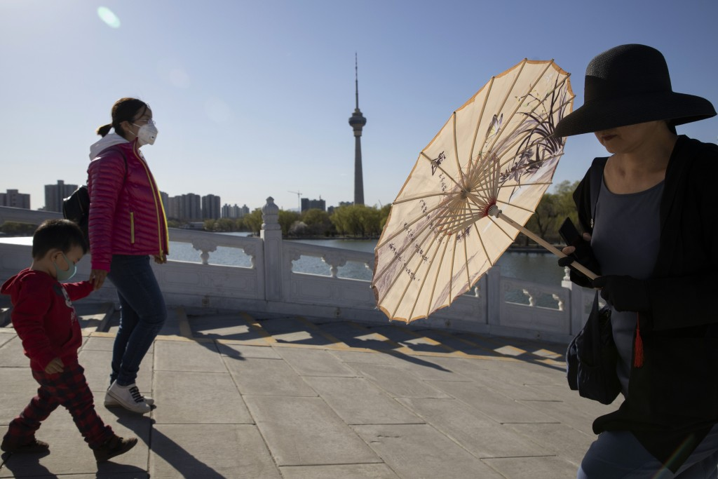 In this photo taken Thursday, March 19, 2020, visitors, some with face masks for protection against the coronavirus, enjoy a sunny day at a park in Be...