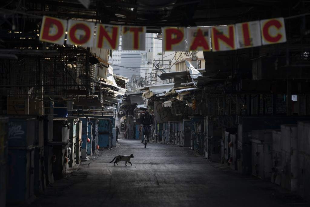 """A """"don't panic"""" sign hang on the entrance of a closed food market that was shut down in order to reduce the spread of the coronavirus, in Tel Aviv, Is..."""