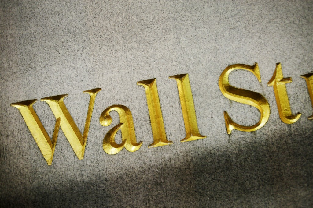 FILE - This Oct. 8, 2014, file photo shows a Wall Street address carved in the side of a building, in New York. The banking system is not as risk of f...