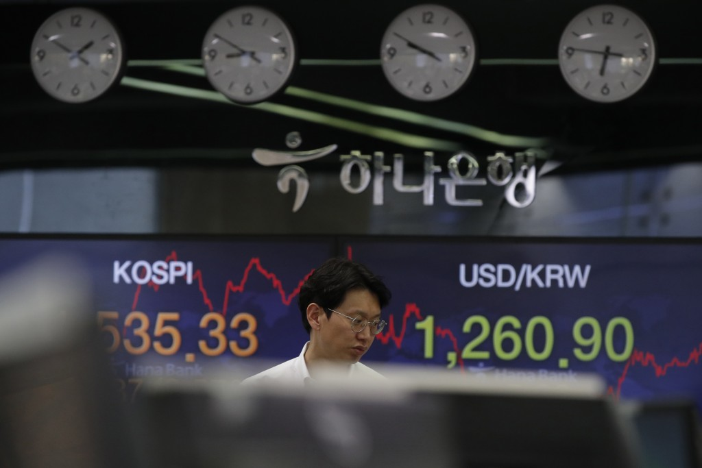 A currency trader walks by screens showing the Korea Composite Stock Price Index (KOSPI), left, and the foreign exchange rate between U.S. dollar and ...