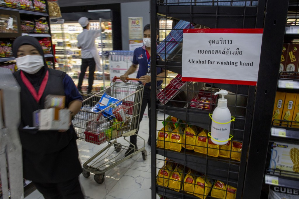 A hand sanitizer container is mounted in store-shelf as staff with face masks place supplies in a supermarket in Bangkok, Thailand, Tuesday, March 24,...