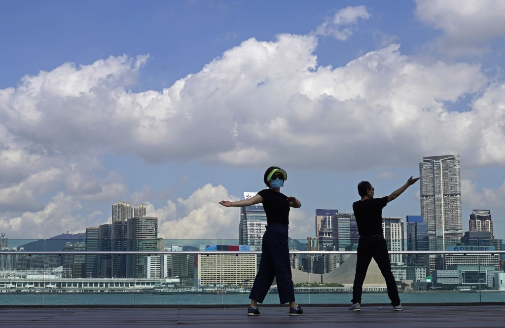People exercise at the waterfront in Hong Kong, Feb. 26, 2020. (AP Photo/Vincent Yu)