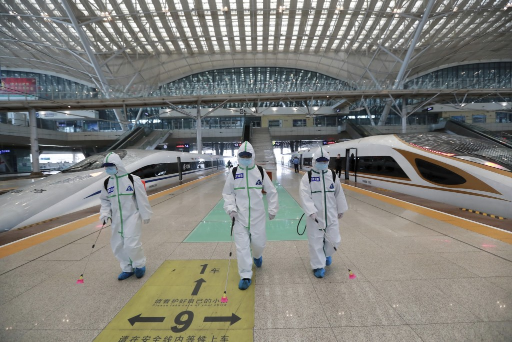 In this photo released by Xinhua News Agency, firefighters conduct disinfection on the platform of Wuhan Railway Station in Wuhan, central China's Hub...