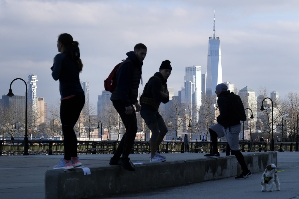 People exercise outdoors with a view of Manhattan in Hoboken, N.J., March 17, 2020. (AP Photo/Seth Wenig)