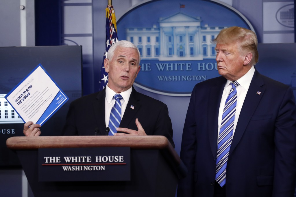 President Donald Trump listens as Vice President Mike Pence speaks about the coronavirus in the James Brady Briefing Room, Monday, March 23, 2020, in ...