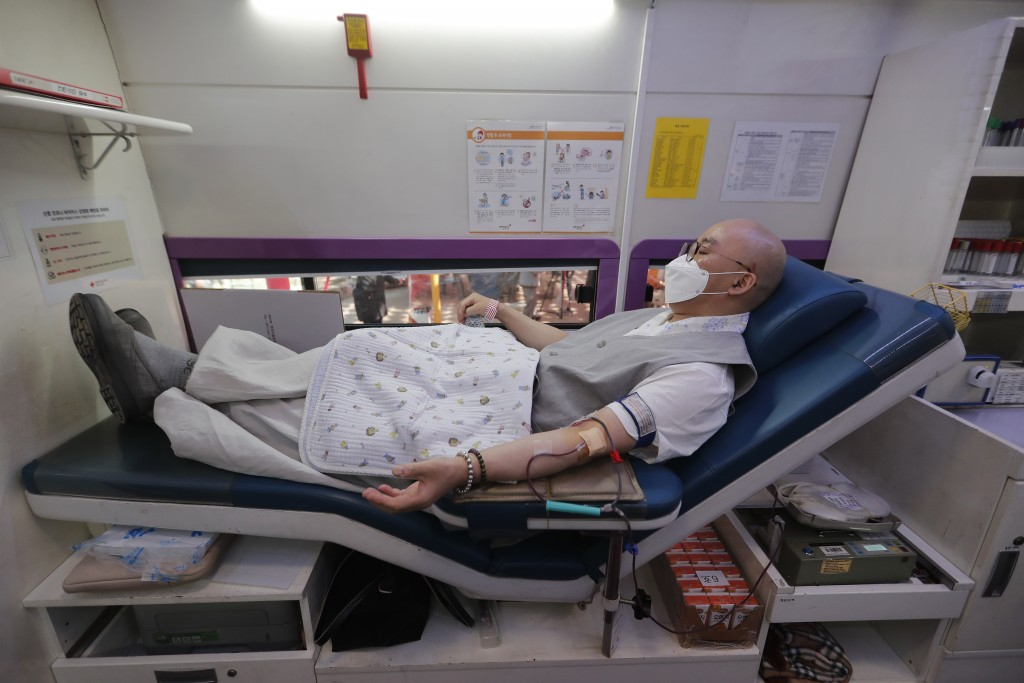 A Buddhist monk wearing a face mask donates blood due to the shortage of blood donators amid the rapid spread of the new coronavirus at the Jogyesa te...