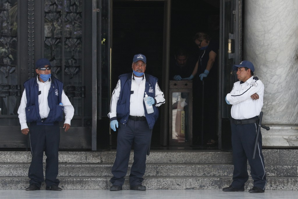 Security guards stand in front of the entrance to the Palace of Fine Arts, now closed to the public, in central Mexico City, Monday, March 23, 2020. B...