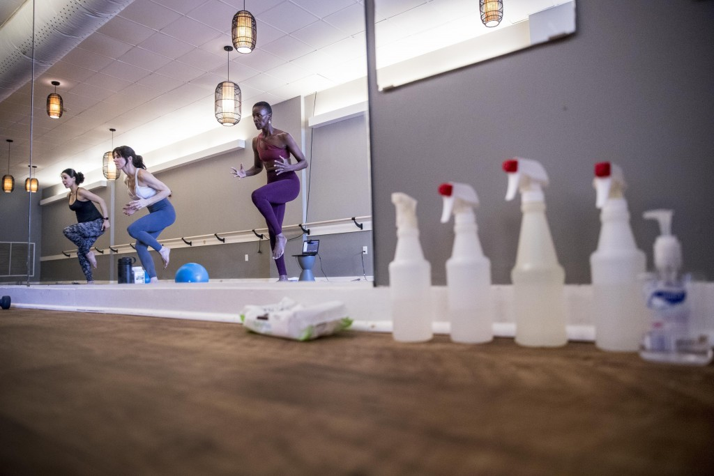 Cleaning products line the wall as Mariam Sufi, left, Lara Atella, second from left, and Lashone Wilson, right, hold an online yoga class via webcam a...