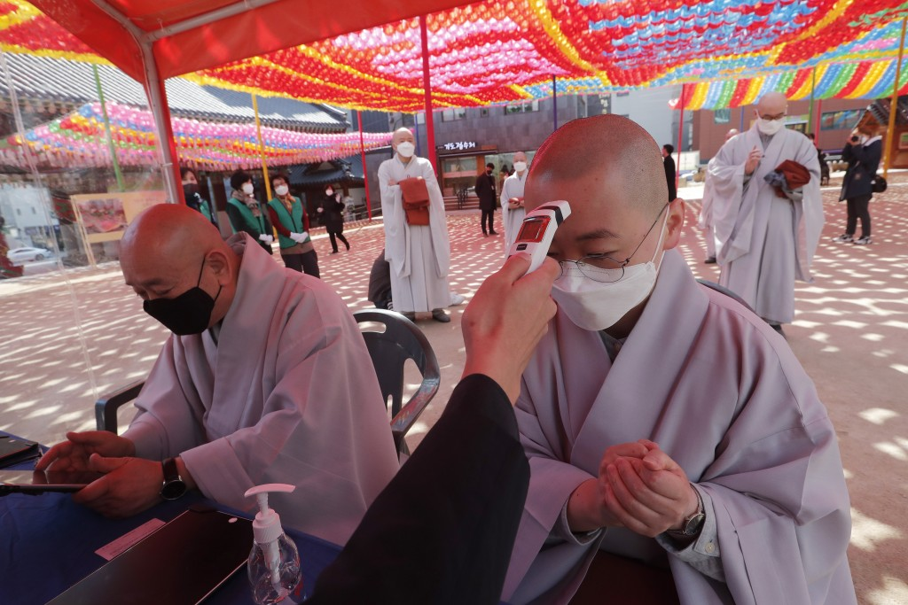 A Buddhist monk wearing a face mask is checked his temperature by a Korea Red Cross official to donate blood due to the shortage of blood donators ami...