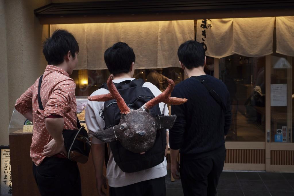 A tourist carrying a souvenir in the shape of deer looks at a restaurant menu in Nara, Japan, Thursday, March 19, 2020. (AP Photo/Jae C. Hong)